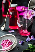 Hibiscus petal syrup being made (a glass of water, a syrup bottle and hibiscus petals)