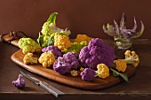 Various different coloured types of cauliflower on a chopping board