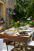 A wooden table in the garden ofa French country house laid with mussels, chips and lemon slices