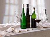 A glass of red wine, bottles of wine and empty glasses