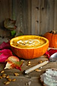 Autumnal pumpkin soup served in a hollowed out pumpkin with sour cream and pumpkin seeds