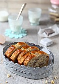 Banana bread, sliced, in a metal basket with baking utensils in the background