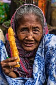 An old Burmese lady eating fried pastry for breakfast (Yangon, Myanmar)
