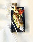 A whole grilled trout filled with lemons