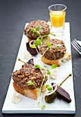 Mini burgers on slices of white bread with capers and beetroot