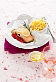 Salmon fillet in parchment paper with lemon, tomatoes and tagliatelle