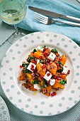 A salad with roasted vegetables, pomegranate seeds and feta cheese
