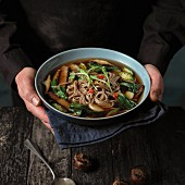 A chef serving beef broth with buckwheat noodles, chillis, bok choy, portobello mushrooms, garlic, okra and water chesrnuts