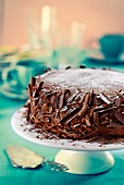 Chocolate cake with grated chocolate and icing sugar on a cake stand