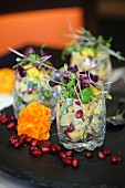 Fruity potato salad in glasses with pomegranate seeds and mixed bean sprouts