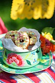 Mini doughnuts with icing sugar in a colourful tin for a summer party