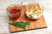 Chilli paste, sliced vegetables and spring onions on a chopping board