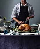 A man carving a roast turkey