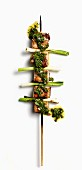 A pork belly skewer with spring onions and salsa verde