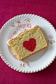 A slice of sponge cake decorated with red heart for Valentine's Day