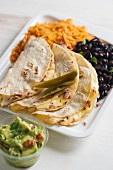 Quesadillas filled with cheese served with black beans, tomato rice and guacamole