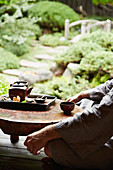 A man sitting cross-legged at a small tea table in a zen garden