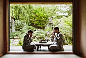 A young couple wearing kimonos sitting cross-legged on a terrace in a zen garden drinking tea