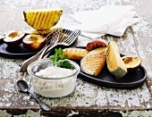 Grilled exotic fruit with a quark dip on an old table
