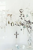 Glass vase of shiny silver Christmas decorations hanging from white-painted twigs