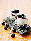 A layered dessert with cherries on a piece of bark