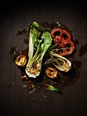 Grilled vegetables on a brown metal surface (bok choy, red peppers, halved, yellow habaneros) with a sprig of thyme
