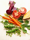 An arrangement of vegetables featuring peas, carrots, spinach, tomatoes and beetroot
