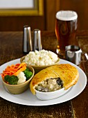 Chicken and mushroom pie with vegetables and mashed potatoes in a pub