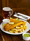 Fish and chips with sauces and beer in a pub