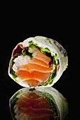A spring roll with salmon, onions and lettuce