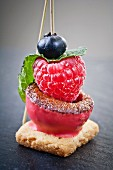 Raspberry ice cream with a fruit skewer on a biscuit