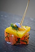 A salmon and mango skewer with herbs