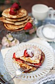 Pancakes with strawberries and icing sugar