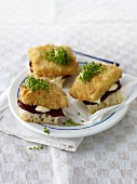 White bread topped with breaded fish fillet, beetroot and cress
