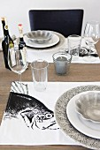 White and grey place setting with fish motif on place mat