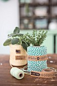 A roll of twine decorated with a bunch of fresh herbs and sticky tape