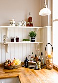 Fruit bowl next to tray of condiments on kitchen counter below bracket shelves on white wooden wall