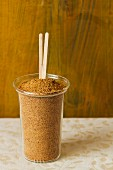 Coconut flower sugar in a glass with wooden sticks