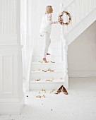 Woman wearing white clothing in snow-white stairwell