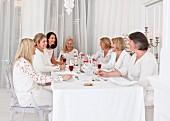 Women dressed in white with red drinks sitting at a table laid with a white cloth