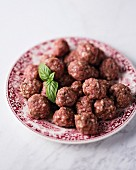 A plate of raw mini beef meatballs