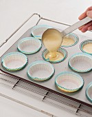 Cupcake mixture being poured into baking cases