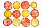 Sliced oranges and pink grapefruits on a backlit surface