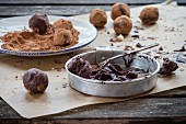 Homemade chocolate truffles with ingredients on an old wooden table