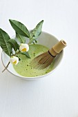 Matcha tea with a bamboo whisk in a tea bowl on a white surface