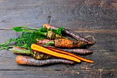 Various types of carrots on a wooden surface