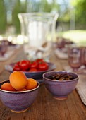 Purple bowls of apricots, olives and tomatoes