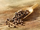 Allspice berries on a wooden scoop
