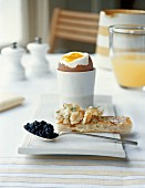 A soft boiled egg and a slice of toast with smoked salmon and caviar