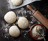 Four pizza dough balls on a baking tray with flour and a rolling pin
